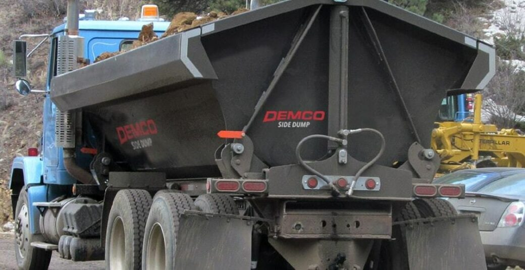 Side dump truck box on truck chassis